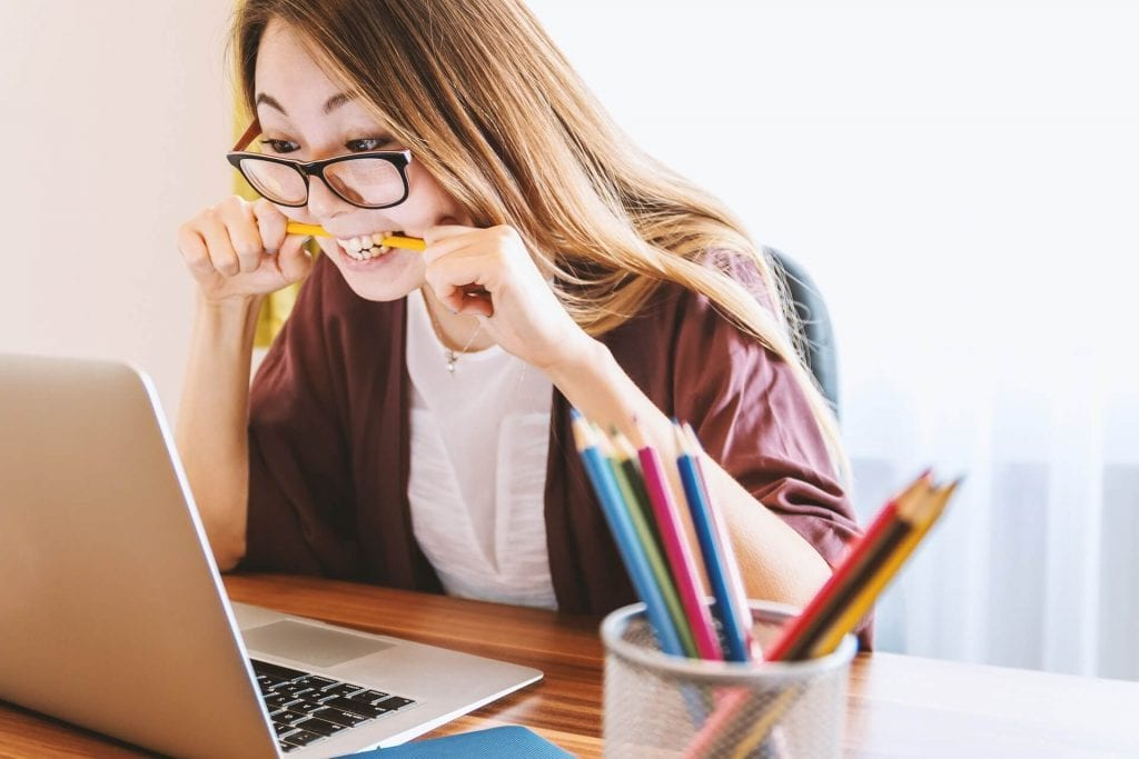 Girl biting pencil in front of laptop