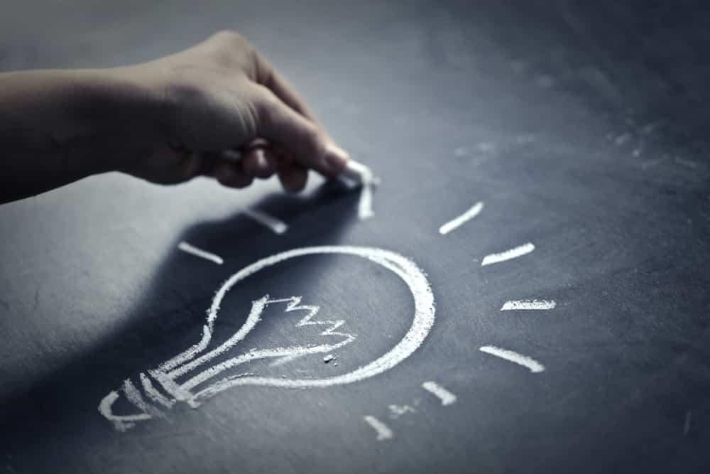 drawing a lightbulb on a chalkboard